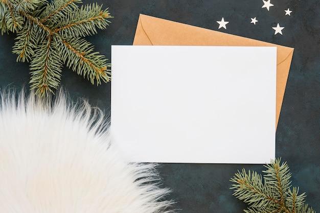Carte et enveloppe à côté des aiguilles de pin