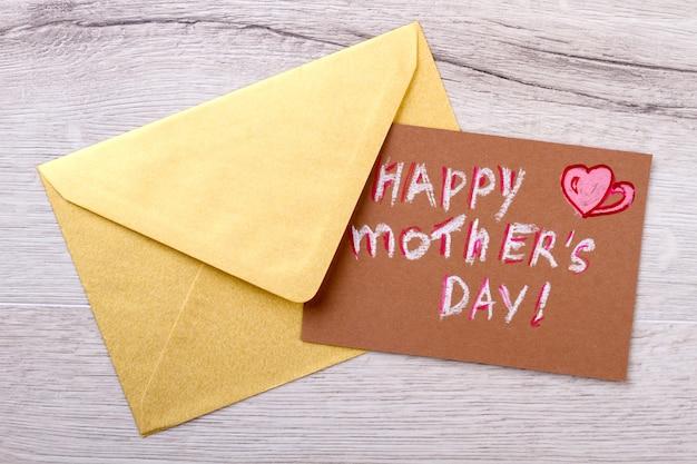 Carte et enveloppe pour la fête des mères. enveloppe sur fond de bois. n'oubliez pas d'envoyer des salutations. lettre de félicitations pour maman.