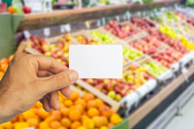 Carte d'épicerie en plastique vide à la main sur la carte d'épicerie de fond de supermarché pour des remises et des promotions...