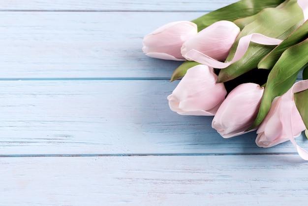 Carte de félicitation festive avec une fleur de tulipes roses tendre fraîche sur un fond en bois bleu pastel.