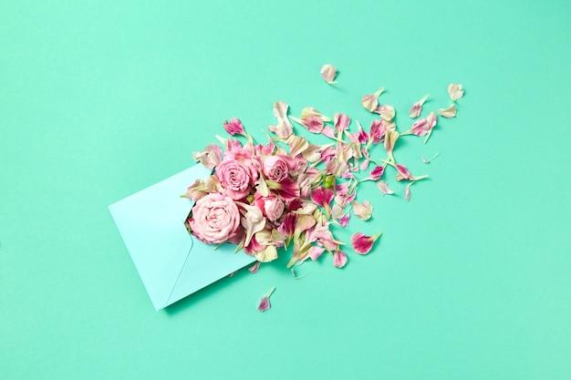 Carte de félicitations avec enveloppe artisanale avec des roses fraîches et des pétales sur fond turquoise, copiez l'espace. vue de dessus.
