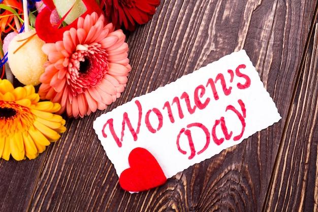 Carte de fête de la femme avec coeur. papier de voeux près de gerbera. célébrez et offrez des cadeaux. fleurs et bonbons pour les femmes.