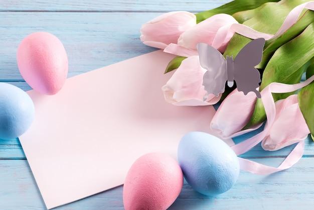 Carte de fête de joyeuses pâques d'oeufs peints, de feuilles de papier et de papillons artisanaux.