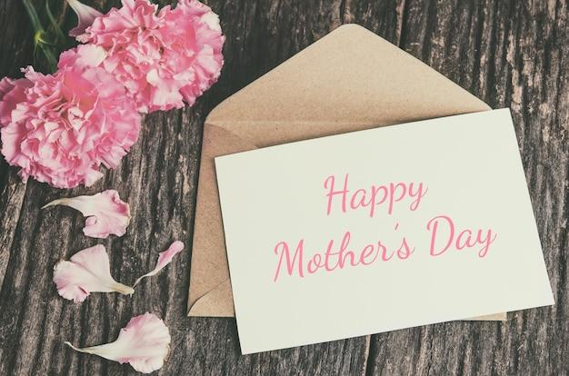 Carte de fête des mères heureuse avec enveloppe brune et fleurs d'oeillets roses