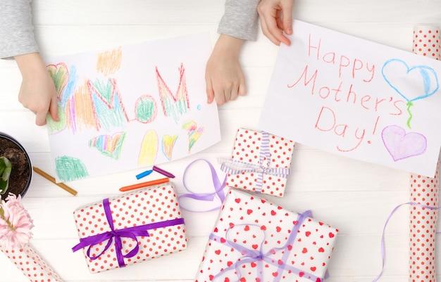 Carte de fête des mères heureuse faite par petit enfant. les mains de la fille tenant des cartes faites à la main avec des coffrets cadeaux.