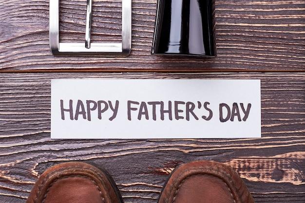 Carte de fête des pères près des chaussures. cologne près de la ceinture sur bois. développement de la mode masculine.