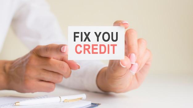 Carte 'fix you credit' dans les mains de la femme. affaires, éthique, publicité, marketing.