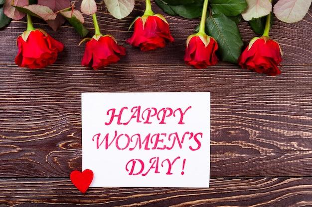 Carte et fleurs de la fête de la femme. roses de couleur rouge. faites une surprise pour la femme. cadeau simple mais élégant.