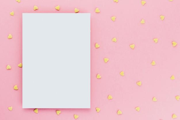 Carte sur un fond de confettis de confiserie en forme de coeur sur un espace de copie de fond rose. coeurs jaunes