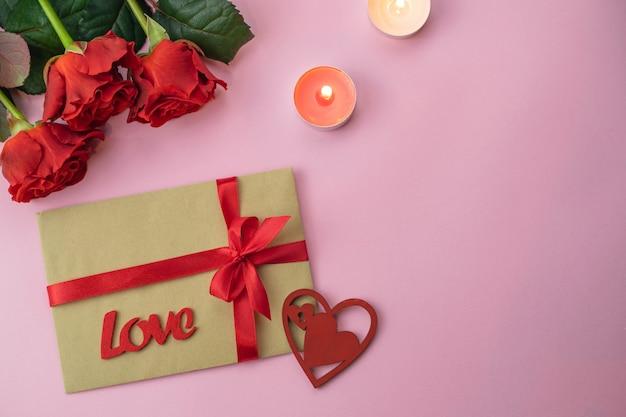 Carte de fond rose saint valentin romantique avec bouquet de belles roses rouges et enveloppe cadeau amour