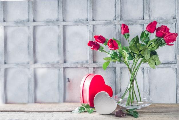 Carte de fond de saint valentin avec boîte-cadeau et bouquet de fleurs roses
