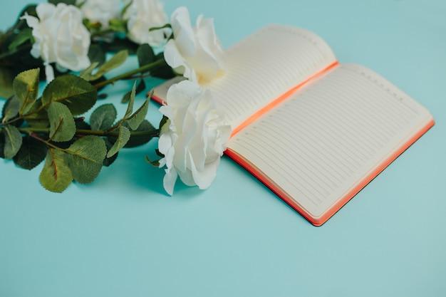 Carte de fraîcheur de printemps. roses blanches avec des feuilles vertes. bouquet de roses blanches à longue tige. roses et cahier.