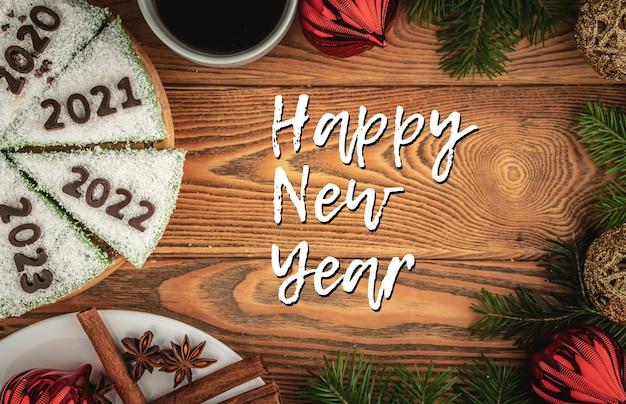 Carte avec gâteau festif décoré de chiffres désignant les années 2020, 2021, 2022, 2023 en chocolat et l'inscription happy new year. vue de dessus.