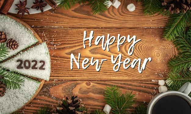 Carte avec un gâteau de fête blanc décoré de copeaux de noix de coco imitant la neige, le numéro 2022 en chocolat et l'inscription happy new year. vue de dessus.