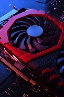 Carte graphique de jeu d'ordinateur, carte vidéo avec deux refroidisseurs sur circuit imprimé, fond de carte mère. fermer. avec un éclairage rouge-bleu.