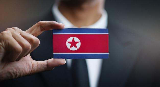 Carte de holding homme d'affaires du drapeau de la corée du nord