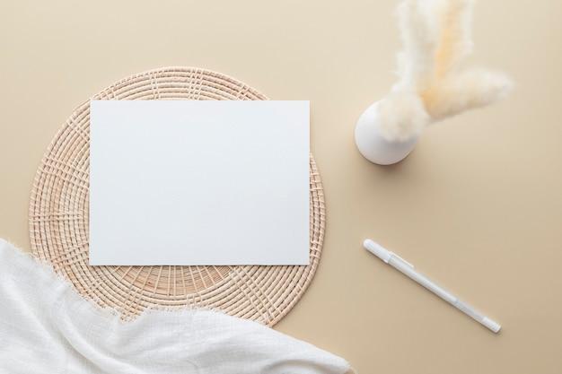 Carte d'invitation blanche, maquette de papier vierge sur fond beige, herbe de roseaux dans un vase, couverture blanche, panier en rotin, mise à plat, vue de dessus, espace de copie
