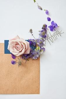 Carte d'invitation de mariage, enveloppe artisanale, fleurs sur fond blanc. vue aérienne. mise à plat, vue de dessus