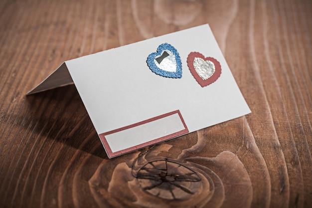 Carte d'invitation en papier blanc sur bois