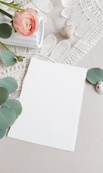 Carte d'invitation de voeux de mariage blanc vierge feuilles d'eucalyptus argenté branche, fleur renoncule rose renoncule rose sur fond de table en papier texturé. modèle moderne élégant vue de dessus plate