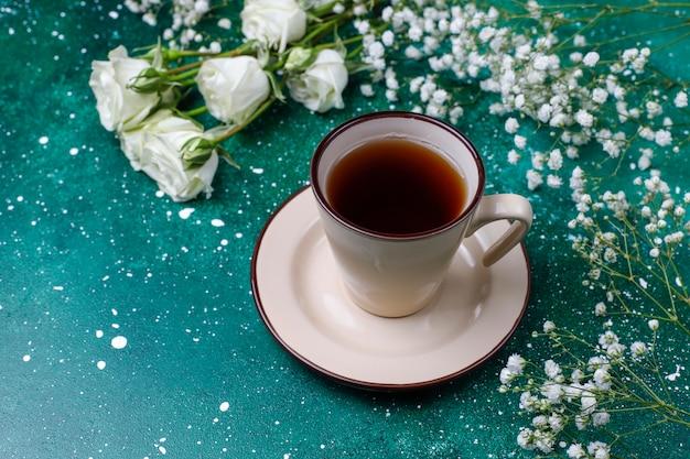 Carte de la journée de la femme du 8 mars avec des fleurs blanches, des bonbons et une tasse de thé