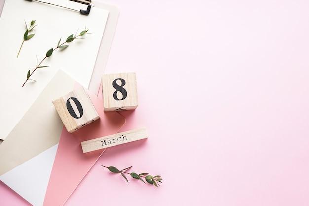 Carte de la journée des femmes, calendrier en bois avec bloc-notes sur fond rose avec espace copie, mise à plat. 8 mars, journée internationale de la femme.
