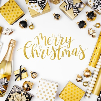Carte de joyeux noël. fond plat de noël ou de fête avec des coffrets cadeaux, une bouteille de champagne, des arcs, des décorations et du papier d'emballage aux couleurs or et noir. mise à plat, vue de dessus