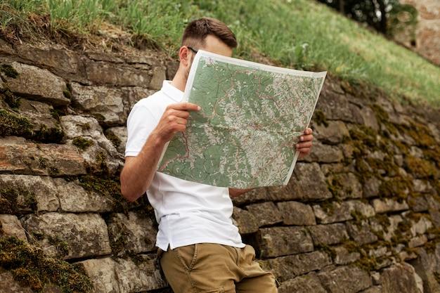 Carte de lecture de jeune homme faible angle