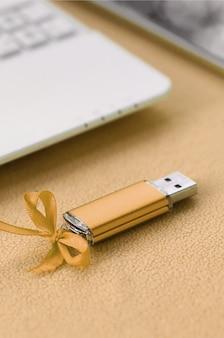 Une carte mémoire flash usb orange avec un nœud bleu repose sur une couverture en molleton doux et à poil orange clair à côté d'un ordinateur portable et d'un smartphone blancs.