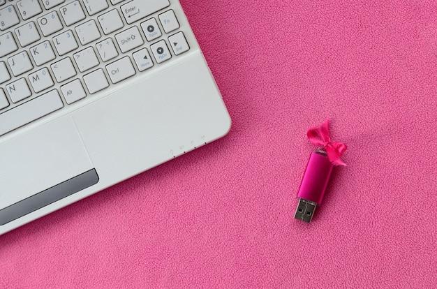 Une carte mémoire flash usb rose brillante avec un noeud rose repose sur une couverture en molleton doux et velu rose pâle à côté d'un ordinateur portable blanc. conception classique de cadeau féminin pour une carte mémoire