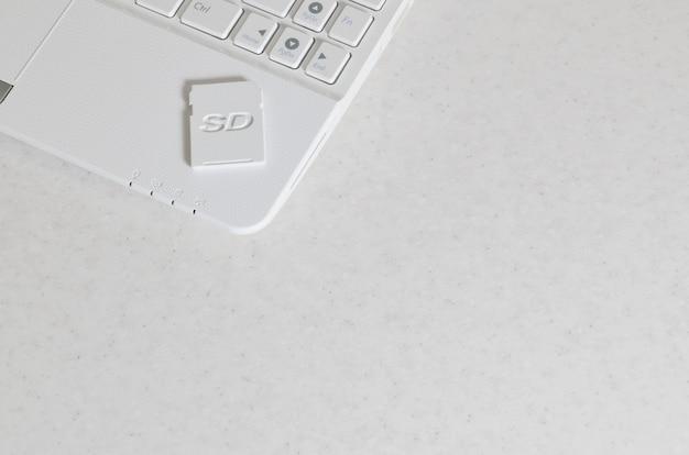 Une carte mémoire sd compacte repose sur un netbook blanc. le