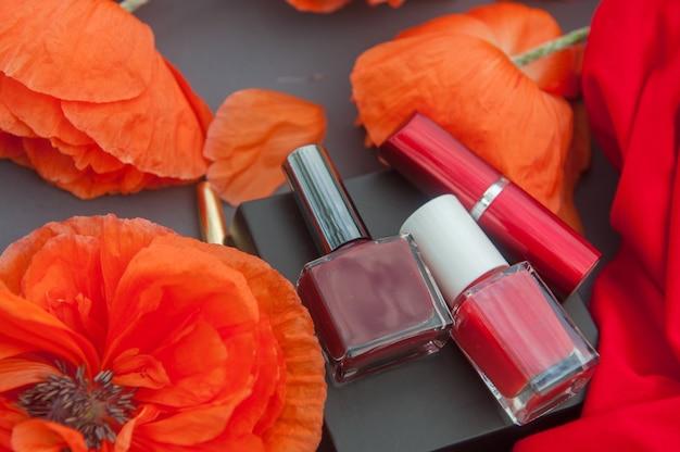 Carte de mode avec des coquelicots rouges et des cosmétiques de couleur rouge