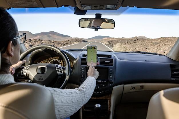 Carte de navigation féminine méconnaissable sur smartphone tout en conduisant un véhicule sur route en campagne