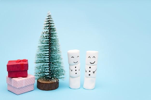 Carte de noël bonhommes de neige près d'un arbre de noël avec des boîtes de cadeaux.