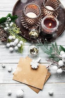 Carte de noël et bonne année avec bougies, pin, sapin sur fond en bois blanc, vue du dessus