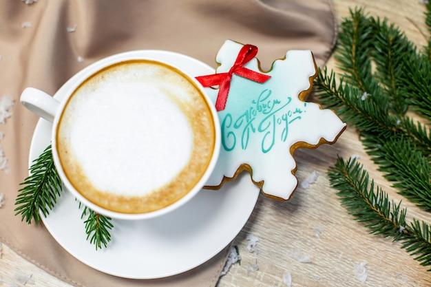 Carte de noël et bonne année avec une tasse de café, pin, branche de sapin et pain d'épice sur une table en bois