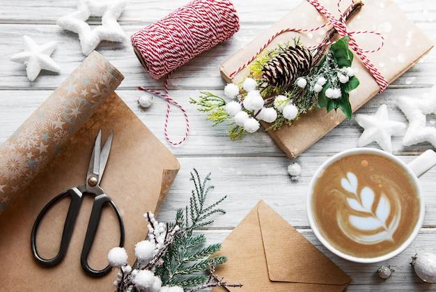 Carte de noël et bonne année avec tasse de café, pin, sapin, coffrets cadeaux sur fond de bois blanc, vue du dessus