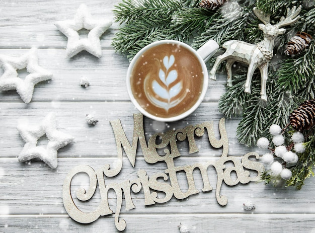 Carte de noël et bonne année avec tasse de café, pin, sapin sur fond en bois blanc, vue du dessus