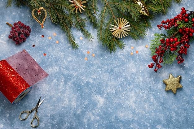 Carte de noël avec des branches de sapin, des rubans et des décorations rouges, des ornements en bois, des confettis. mise à plat de noël