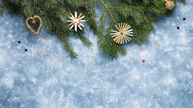 Carte de noël avec des branches de sapin, des rubans rouges et des décorations, des ornements en bois, des confettis avec de la neige. mise à plat de noël