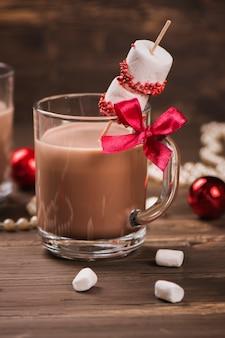 Carte de noël: chocolat chaud avec des guimauves sur fond vintage rustique.