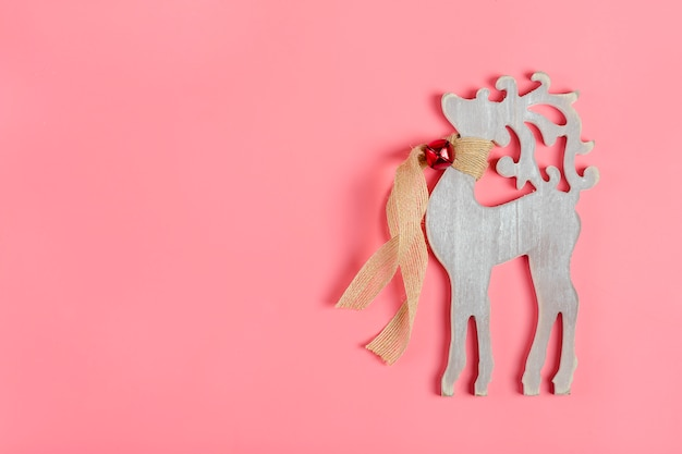 Carte de noël. décor de nouvel an - cerf en bois avec une écharpe et une cloche autour du cou sur rose