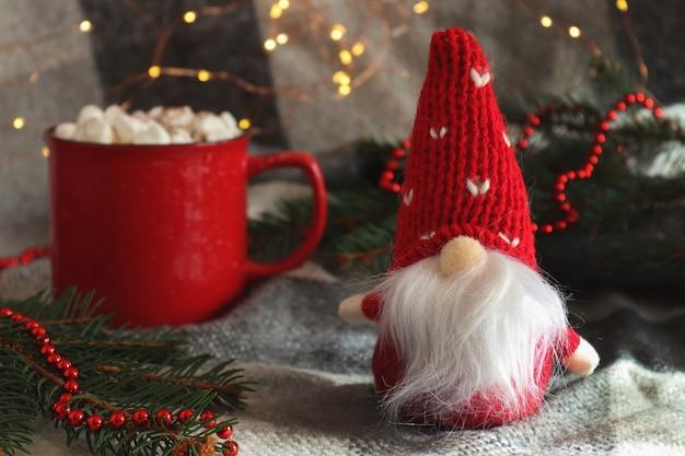 Carte de noël drôle avec gnome jouet une tasse de chocolat chaud avec des guimauves et des branches de sapin