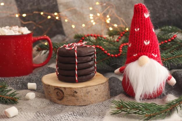 Carte de noël drôle avec toy gnome tasse de chocolat chaud avec des biscuits aux guimauves sur coupe en bois