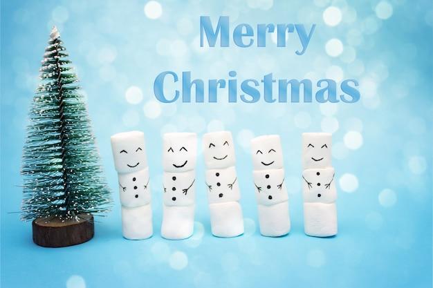 Carte de noël joyeux avec des bonhommes de neige près de l'arbre de noël