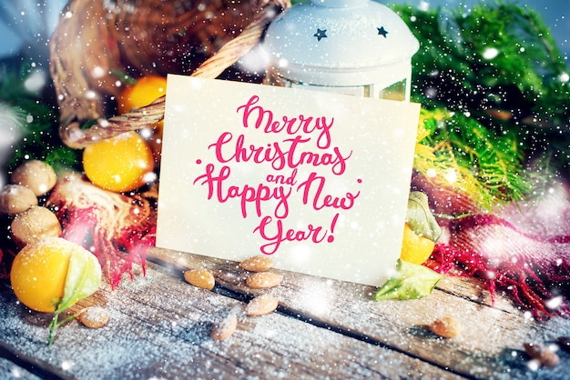 Carte de noël avec message joyeux noël et bonne année. lettre, épicéa, lanterne, mandarines, noix sur fond en bois. flocons de neige dessin décorés