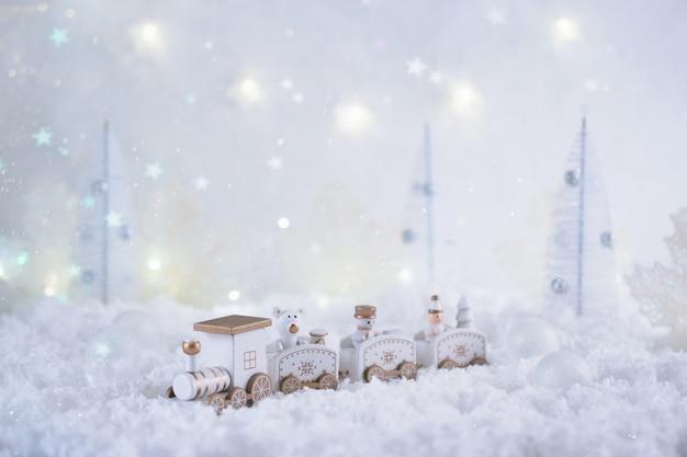 Carte de noël avec petit train dans une forêt de fées en hiver avec neige et lumières.