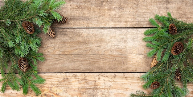 Carte de noël avec pin, branches d'épinette et cônes sur fond de bois vieilli rustique