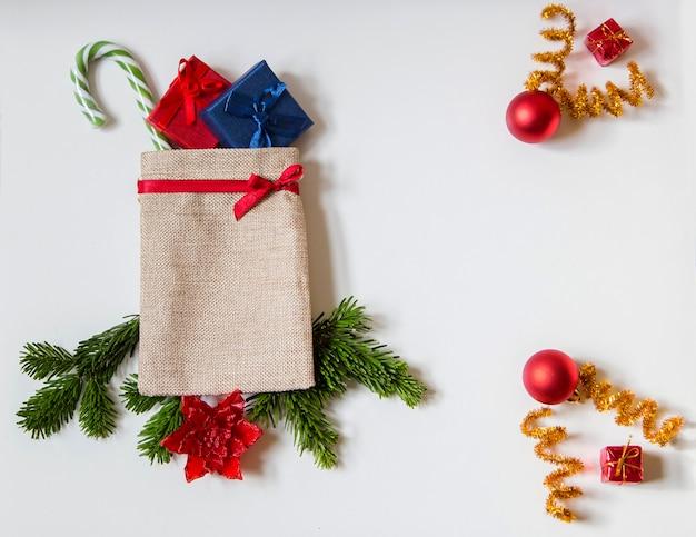 Carte de noël avec un sac de jute rempli de cadeaux et d'espace pour écrire