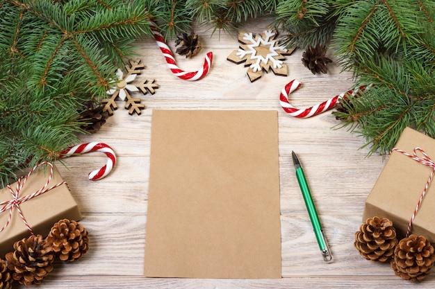 Carte de noël vide sur une table en bois avec des bonbons de noël et des coffrets cadeaux
